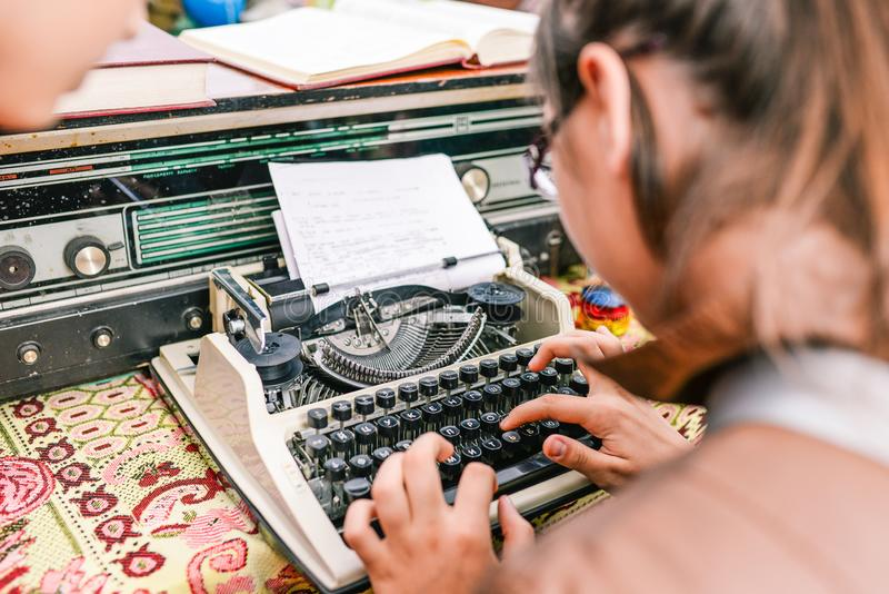 Young girl types on a typewriter. The journalist prints news. Business concept or news royalty free stock image