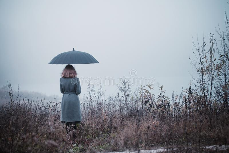 Young girl with umbrella in autumn field stock photo