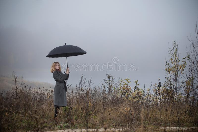 Girl with umbrella in autumn field stock photo