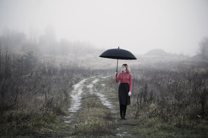 girl with umbrella in autumn field royalty free stock photography