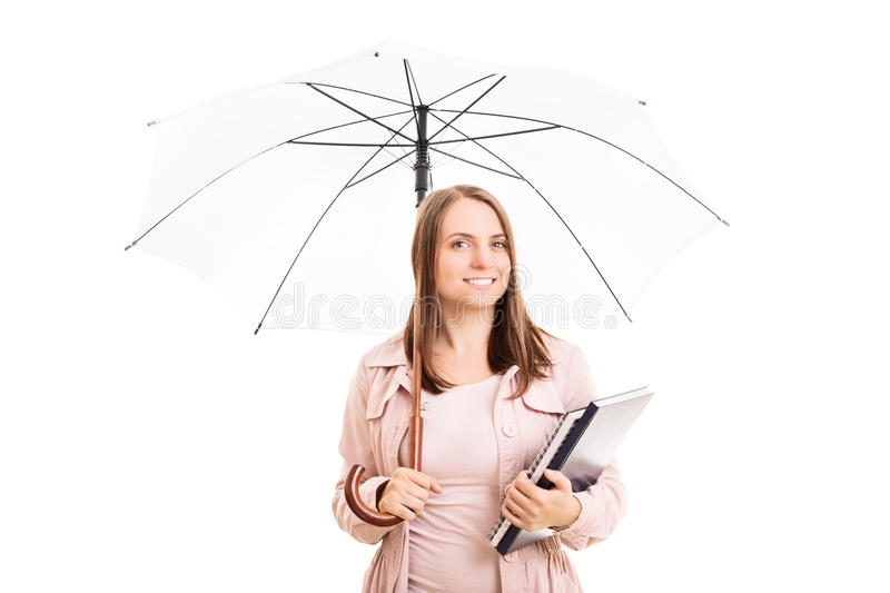 Young girl under an umbrella carrying some notebooks stock image