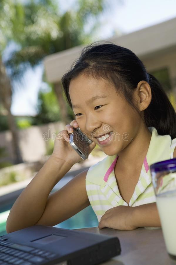 Young Girl Using Laptop and cell phone outdoors stock image