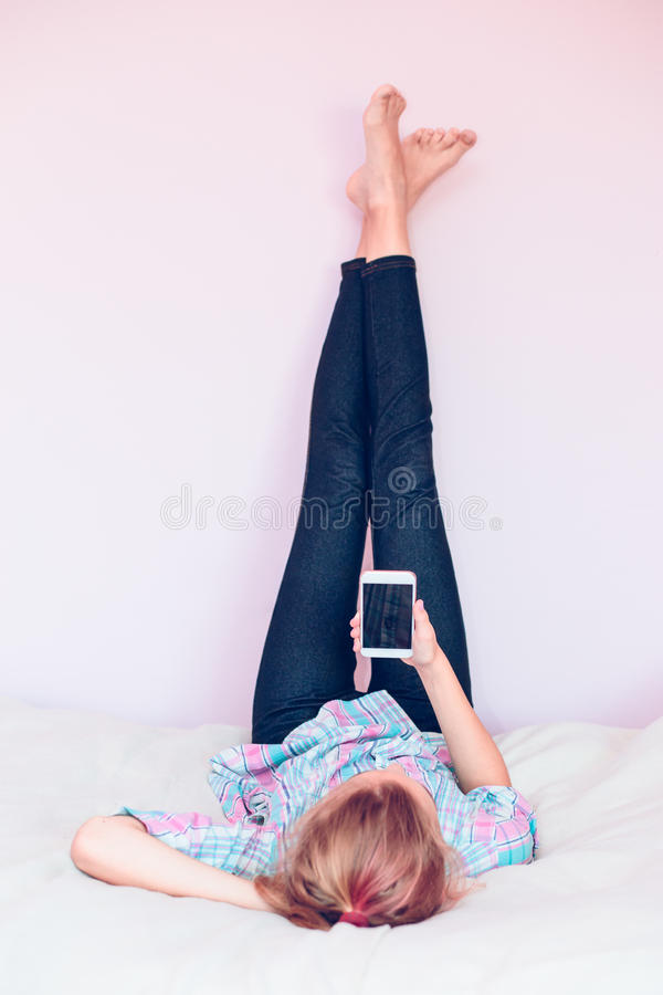 Young girl using mobile phone lying in bed stock images