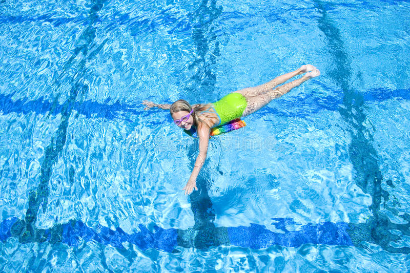 Young girl using paddle board in swimming pool stock photos