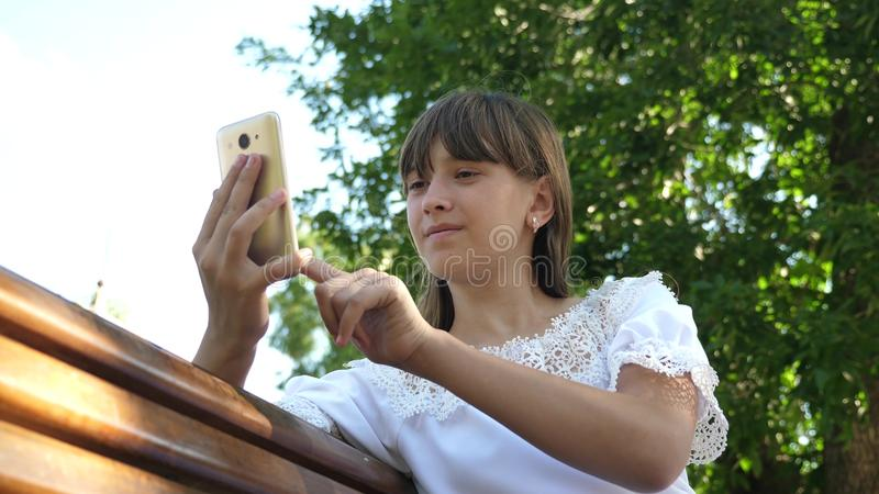 A young girl using a smartphone is writing a letter on a bench in a beautiful green park. Young millennial woman in the. Young girl using a smartphone is writing stock photography
