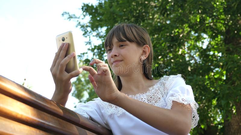 A young girl using a smartphone is writing a letter on a bench in a beautiful green park. Young millennial woman in the. Young girl using a smartphone is writing royalty free stock image