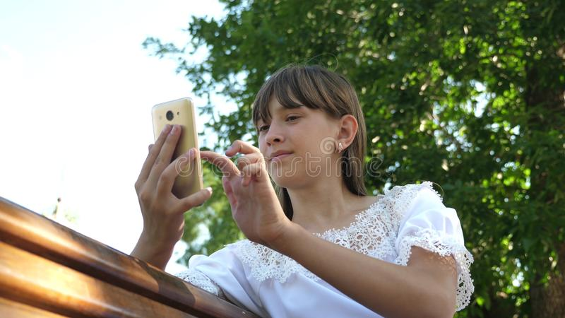 A young girl using a smartphone is writing a letter on a bench in a beautiful green park. Young millennial woman in the. Young girl using a smartphone is writing royalty free stock photo