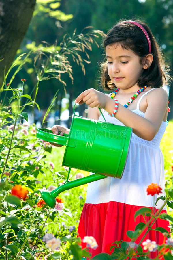 Young Girl Using Watering Can Outdoors. stock photo