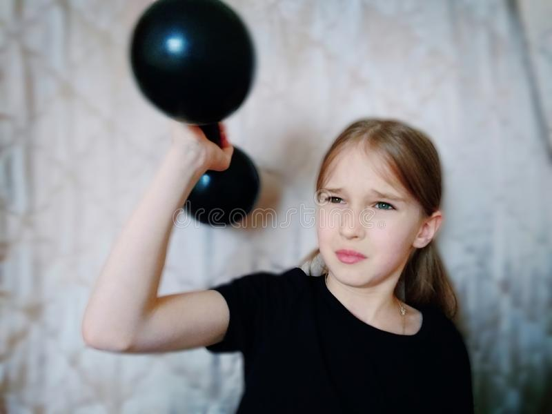 Child with the dumbbell. A young girl is very thin decided to go in for sports. She lifts a very heavy  dumbbell with great difficulty royalty free stock images
