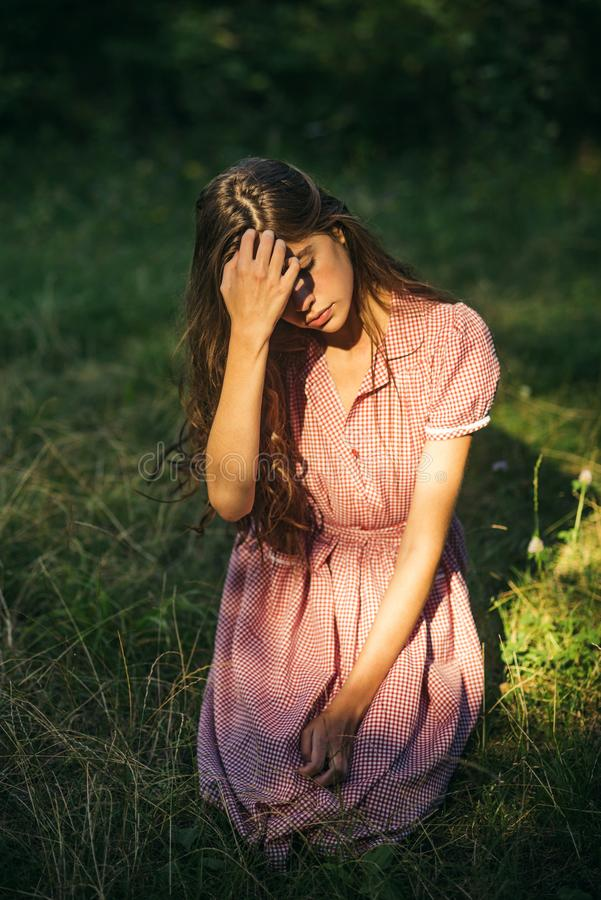 Young girl in vintage dress sitting on grass. Brunette covering her eyes from sun. Beautiful nymph in forest stock photography