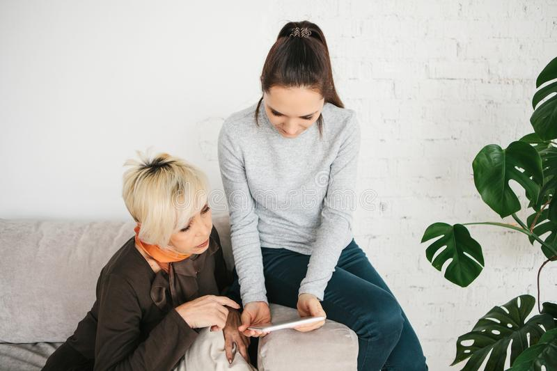 A young girl explains to an elderly woman how to use a tablet or shows some application or teaches you how to use a royalty free stock photography