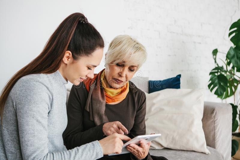 A young girl explains to an elderly woman how to use a tablet or shows some application or teaches you how to use a stock image
