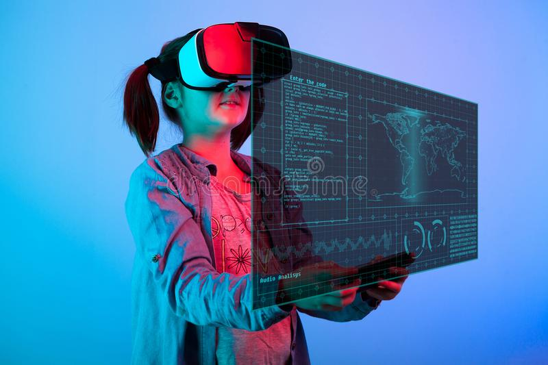 Young girl with a VR headset on the head looking at a futuristic screen in fron of her. And holding a device in hand to control the screen hud royalty free stock images