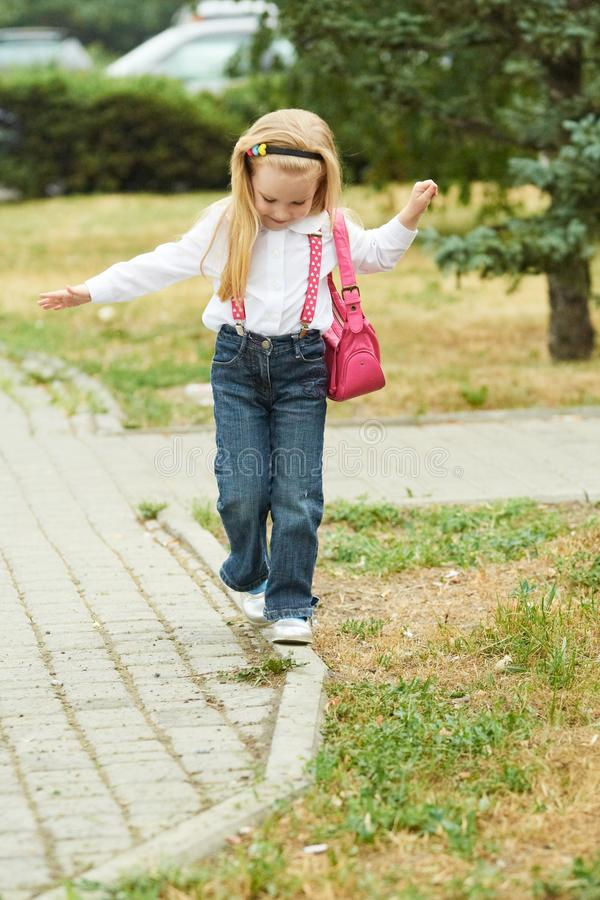 Young girl walk on curb. Jeans, ping bag royalty free stock image