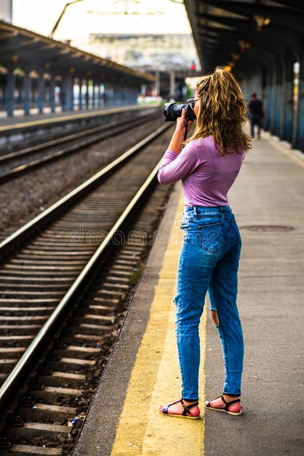 Young girl walking alone on train platform and taking photos on railway station.  stock photo