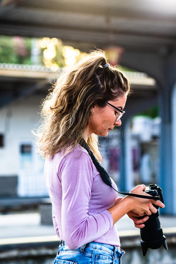Young girl walking alone on train platform and taking photos on railway station.  stock image