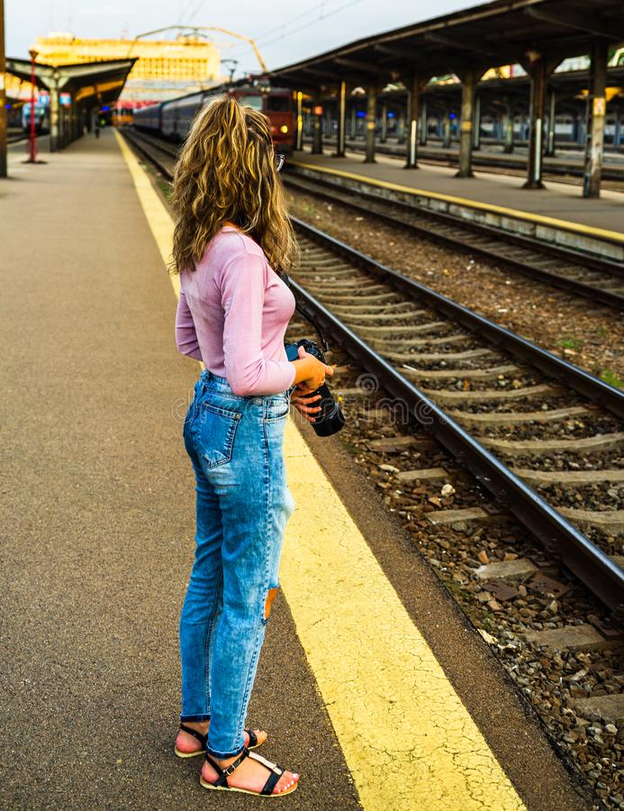 Young girl walking alone on train platform and taking photos on railway station.  royalty free stock photo