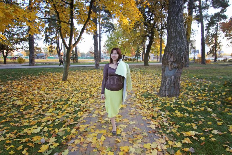 Young girl walking in autumn park. a woman walking on a road with yellow leaves - street covered with yellow autumn stock photos