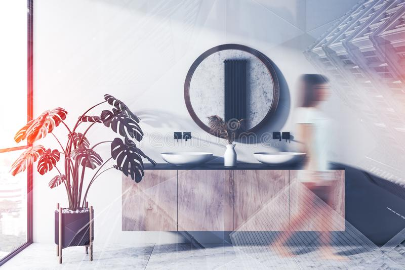 Young girl walking in double sink bathroom. Young woman walking in stylish bathroom interior with double sink standing on wooden countertop and round mirror stock photography
