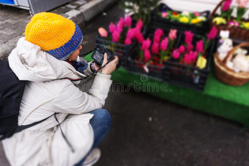 A young girl walking takes a picture of fresh spring flowers, an royalty free stock photos