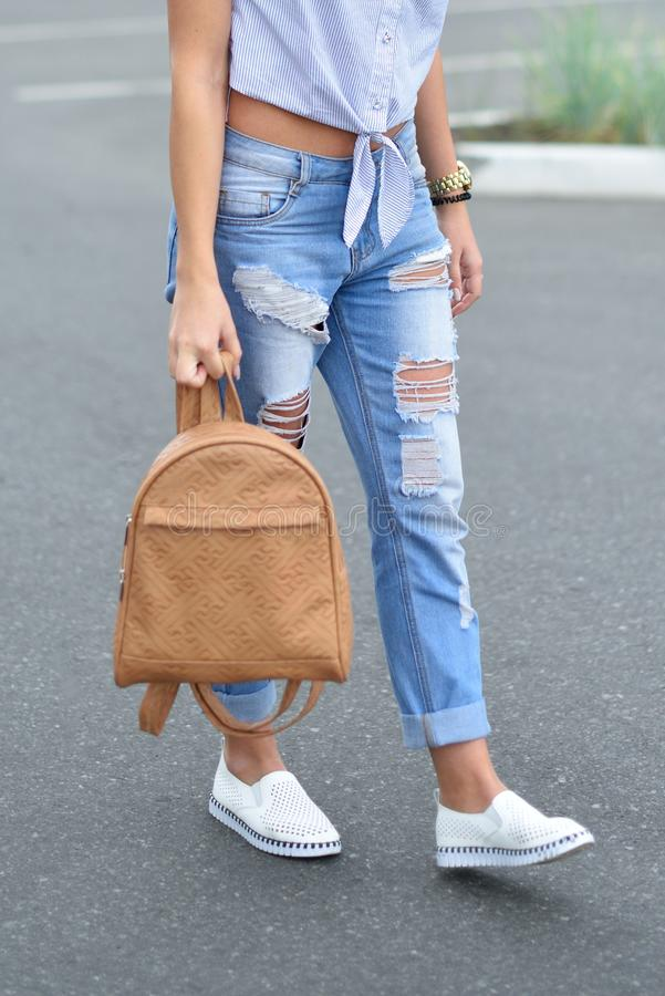 A young girl walks down the street with a beige backpack in torn blue jeans. Fashionable ripped blue jeans on the legs of a teen stock image