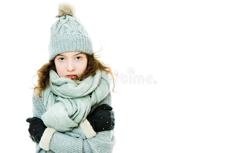 Young girl warming herself by wearing winter cap, gloves. And scarf but still feeling cold stock photography