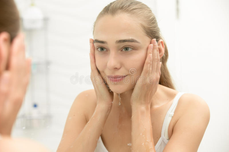 Young girl after washing her face water near the sink. Removed makeup, home bathroom interior, view over shoulder. Reflected at the mirror, splashes running royalty free stock photos