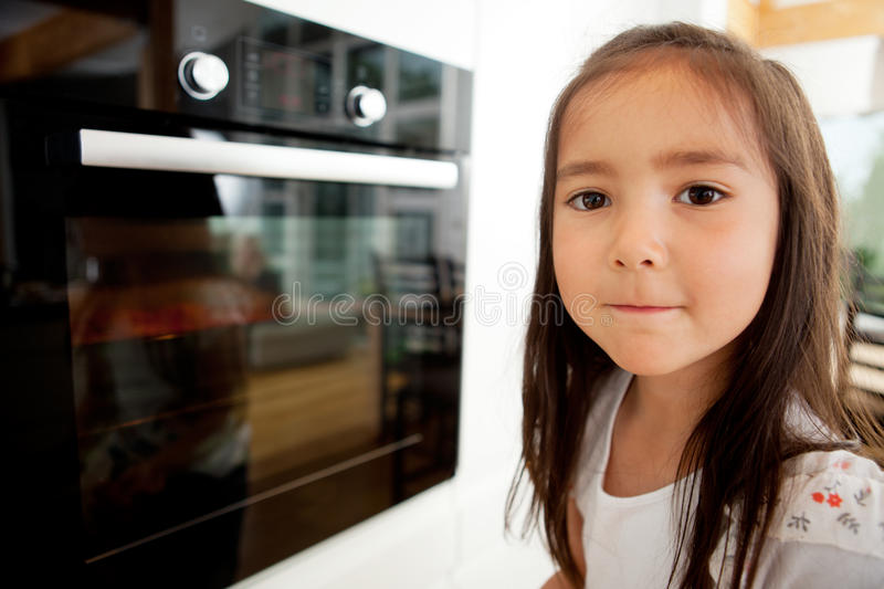 Young Girl Watching Cookies Bake royalty free stock photography