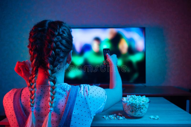 A young girl watching movies with a remote control with a bowl of popcorn on the background of the TV. A bright color of light, royalty free stock photo