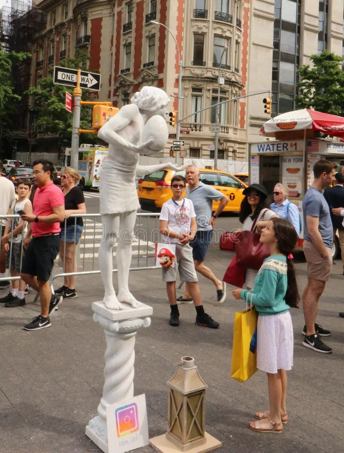 Young Girl Watching a Street Artist. A young girl looks up and smiles at a street artist in New York City stock images