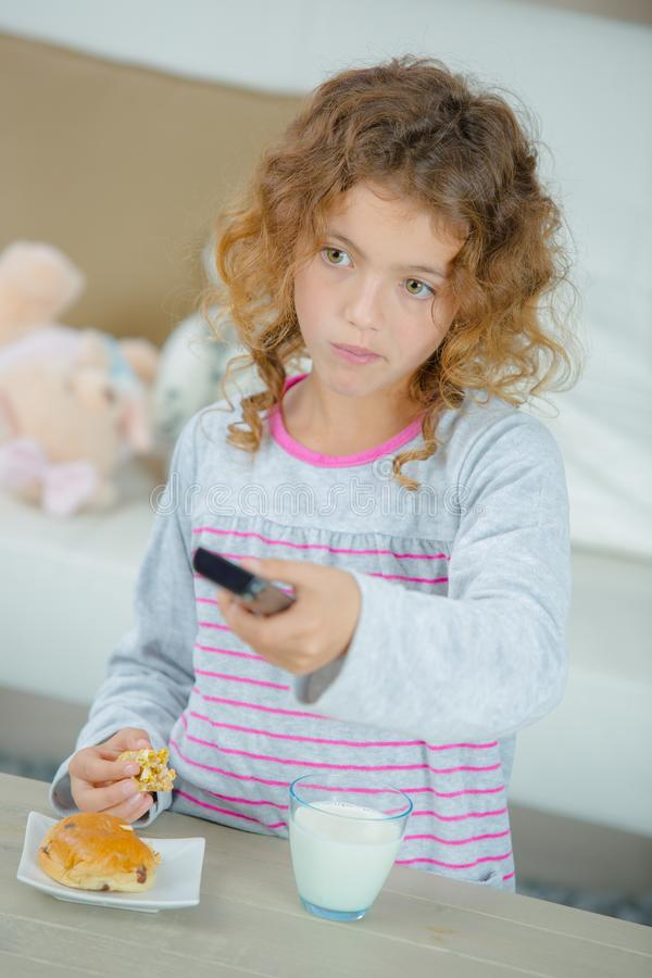 Young girl watching tv while eating royalty free stock photography
