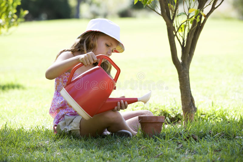 A young girl watering seeds in a plant pot royalty free stock image