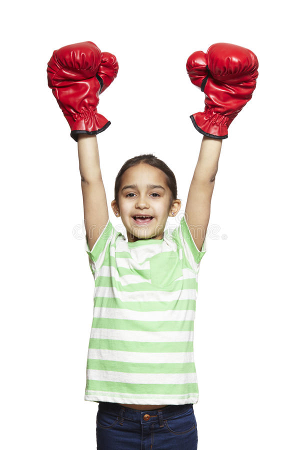 Young girl wearing boxing gloves smiling royalty free stock image