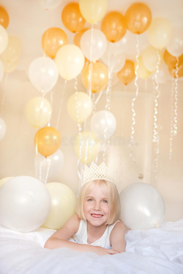 A young girl wearing a crown is surrounded by balloons in the ba royalty free stock image