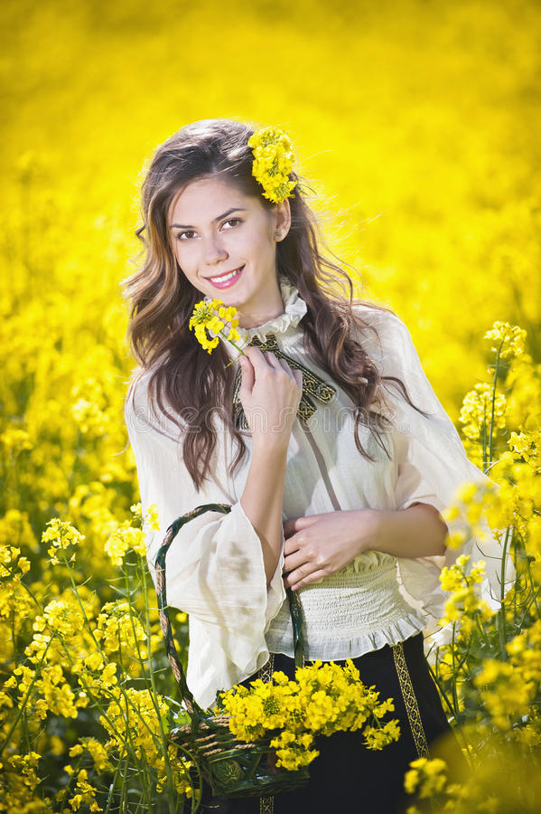 Young girl wearing elegant white blouse posing in canola field, outdoor shot. Portrait of beautiful long hair brunette. With large sleeves in bright yellow stock images