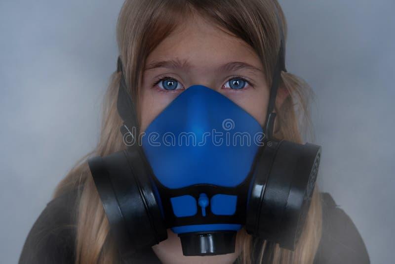 Young girl wearing gasmask, respirator portrait stock image