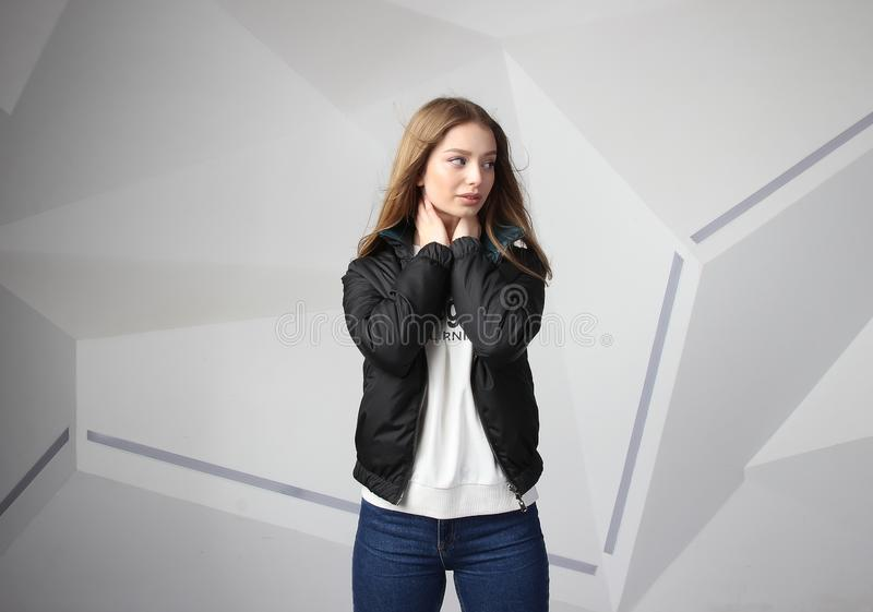 Young girl girl wearing  jacket with area for your logo, mock-up of white women hoodie royalty free stock photography