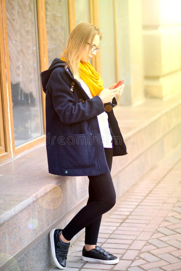 The girl in a blue jacket and a yellow scarf at the facade of th royalty free stock image