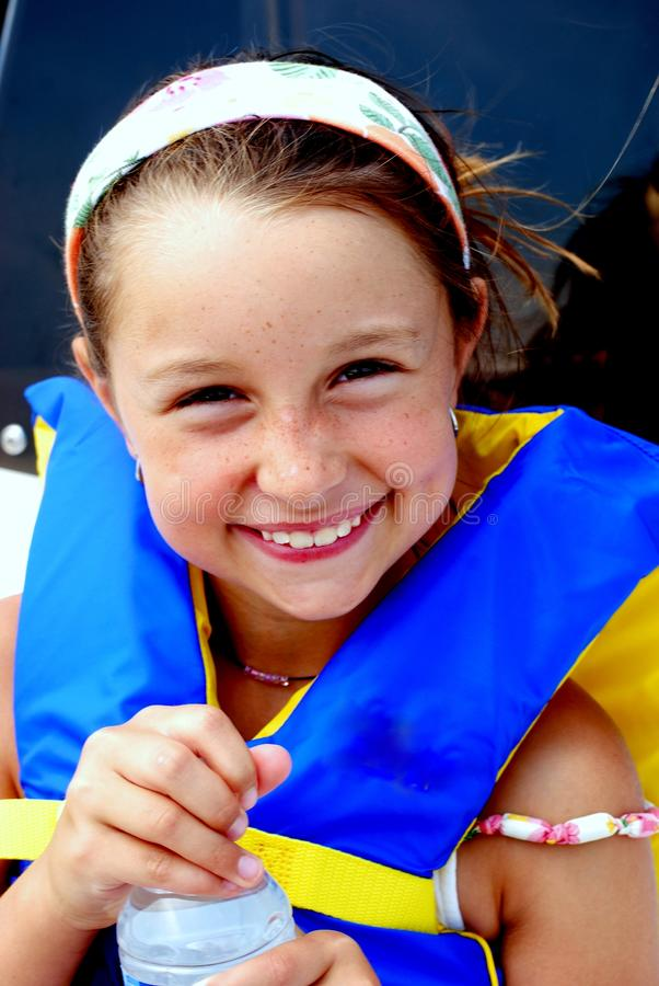 Young girl wearing lifevest holding water bottle. stock photo