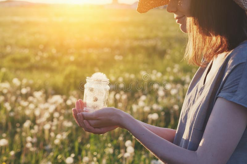 Young girl wearing linen dress holding glass jar full of beautiful fluffy white fresh fragile dandelion flowers, saving happy mome stock photography