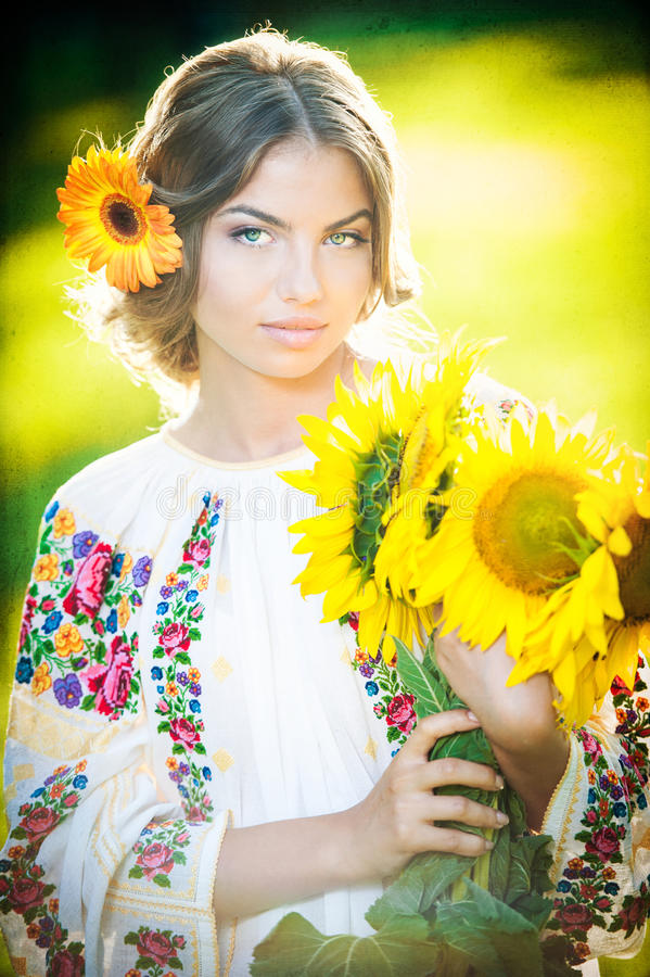 Young girl wearing Romanian traditional blouse holding sunflowers outdoor shot. Portrait of beautiful blonde girl with sunflowers royalty free stock photos