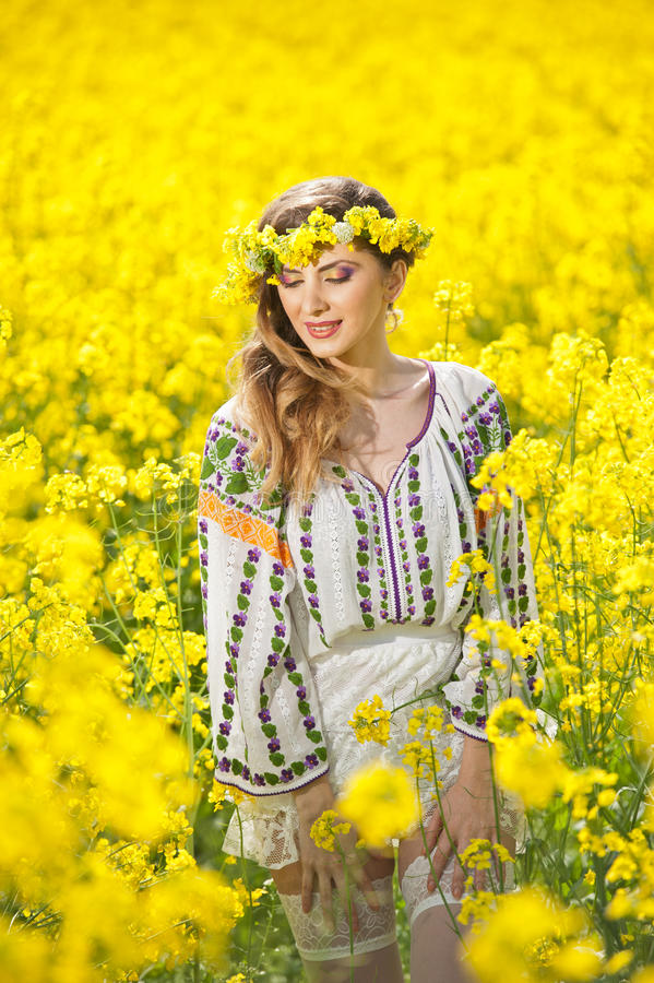 Young girl wearing Romanian traditional blouse posing in canola field, outdoor shot. Portrait of beautiful blonde with wreath royalty free stock image