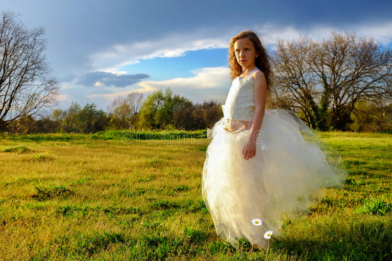 Young girl wearing white dress in late afternoon sun. royalty free stock photos