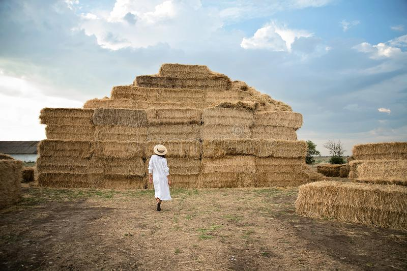Young girl wears summer white dress near hay bale in field. Beautiful girl on farm land. Wheat yellow golden harvest in autumn royalty free stock image