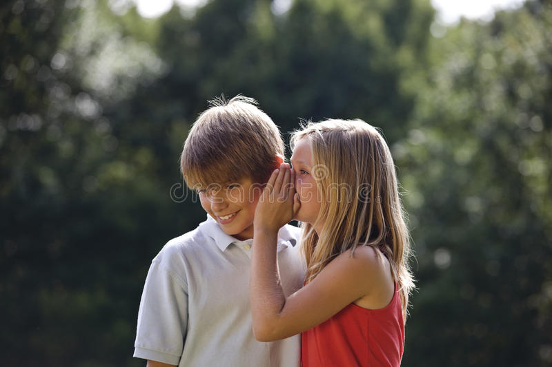 A young girl whispering to a young boy stock photos