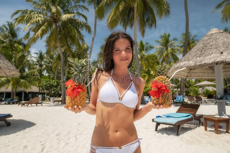 A young girl in a white bathing suit holding two Pinot Colada cocktails in pineapples royalty free stock image