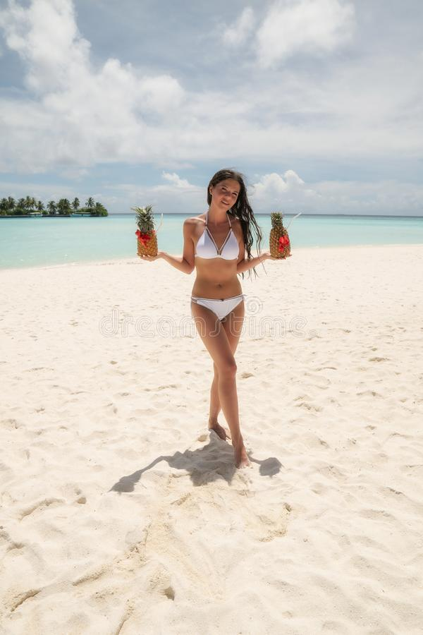 A young girl in a white bathing suit holding two Pinot Colada cocktails in pineapples stock image