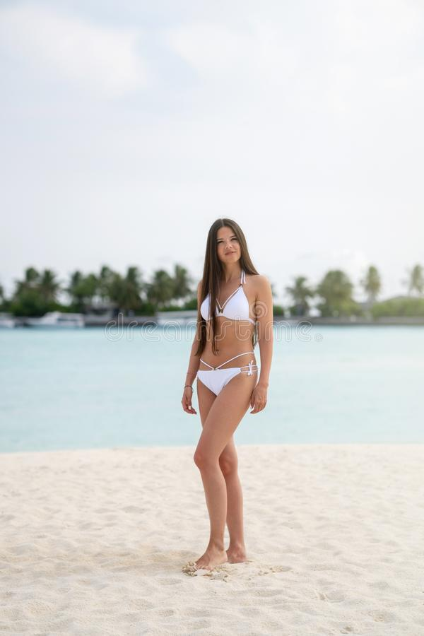 A young girl in a white bathing suit standing on the beach. In the background is turquoise water royalty free stock photo