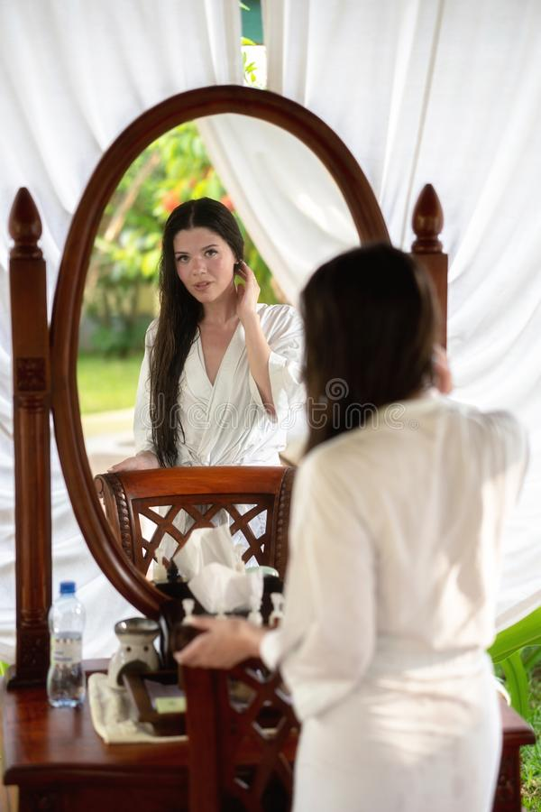 A young girl in a white coat stands in front of a mirror in the outdoor spa stock image
