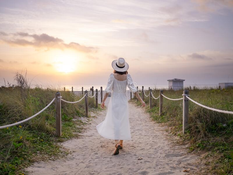 Young girl in a white dress on the beach royalty free stock image